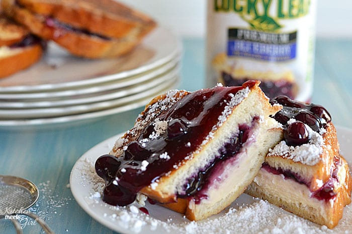 This french toast is stuffed with an easy blueberry cheesecake filling and topped with additional blueberry pie filling. It's perfect for a special occasion! www.kitchenmeetsgirl.com #french toast #cheesecake #recipe